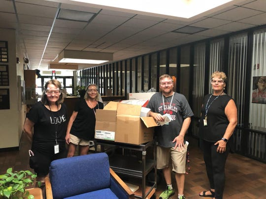 Science teachers from Booker T. Washington High School Pam Hicks (left), Carmen McClammy (middle left), Kevin Turner (middle right) and Cyndee Palacios (right) collected boxes of new, unused safety goggles on Monday, March 30 to donate to Ascension Sacred Heart Hospital.
