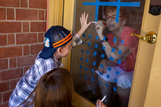 Kathy Holcombe, 66, traces the hand of her granddaughter, Paige Mulvey, 7, through a door window at her home on March 30, 2020, in Phoenix.