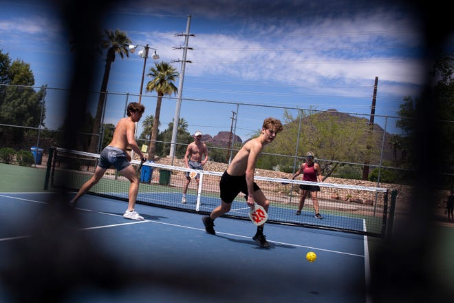 """Kellen Flanigan (left) and Hudson Buth play pickleball with Riley Buth and Colleen Flanigan on the first day of Gov. Doug Ducey's """"stay at home"""" order on April 1, 2020, at G.R. Herberger Park in Phoenix."""
