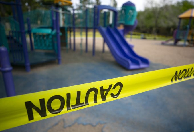 Caution tape surrounds the children's playground equipment at Kachina Park in Phoenix during the first day of the statewide stay at home order on April 1, 2020.
