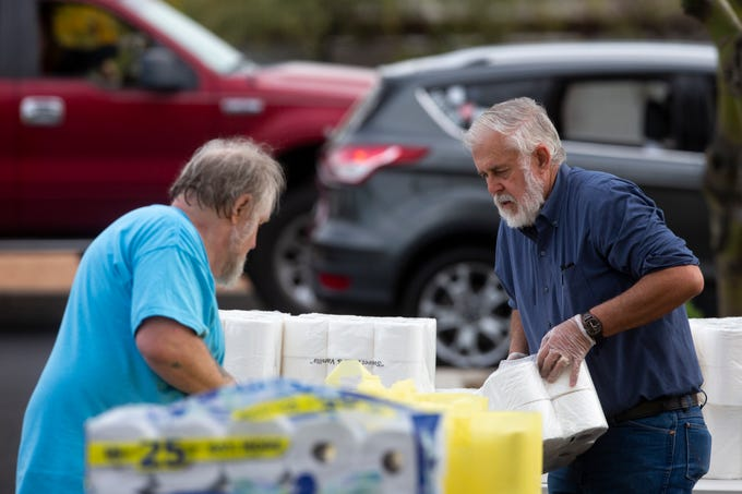 Charles Charlie Swneson (left) and Glendale Mayor Jerry Weiers (right) prepare bags of cleaning supplies to be handed out to those in need at the Vineyard Church of North Phoenix in Glendale, Ariz. on April 1, 2020. Vineyard Church of North Phoenix and Convoy of Hope partnered together to give out non perishable food items and cleaning supplies to those in need during the COVID-19 pandemic.