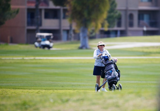 """A golfer pushes her clubs while playing at the Dobson Ranch Golf Club in Mesa on April 1, 2020. Gov. Ducey's """"stay at home"""" order to slow the spread of COVID-19 classify some businesses like golf courses as """"essential"""" during the coronavirus pandemic."""