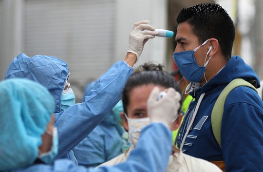 Nurses take the temperature of commuters before entering a bus station in Soacha, on the outskirts of Bogota, Colombia, on April 1. A typical COVID-19 screening process involves taking a subject's temperature, but is not an actual laboratory test to determine if someone has the coronavirus.
