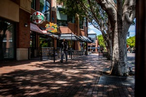 """One man walks down an empty Mill Avenue in downtown Tempe on the first full day of Arizona Gov. Doug Ducey's statewide """"stay-at-home"""" order to slow the spread of the new coronavirus on April 1, 2020."""
