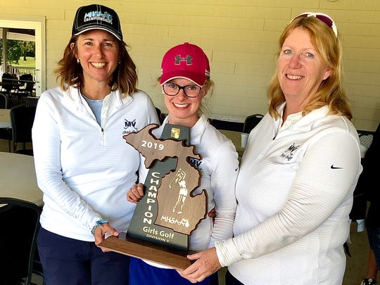 Marysville senior girls golfer Sydney Anger holds the Division 3 regional championship trophy with her coaches.
