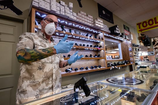Tim Daniels, owner of The Hock Shop in Port Huron, talks about a Sig Sauer P365 handgun Wednesday, April 1, 2020, in his shop's showroom. Daniels said he's seen an increase in easy-to-use guns and first-time gun buyers during the coronavirus lockdown.