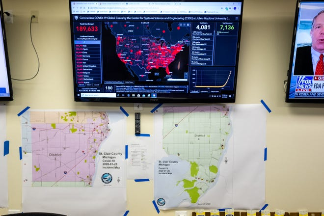A screen displaying statistics of the spread of coronavirus is hung on the wall above different maps in St. Clair County's emergency operation center Wednesday, April 1, 2020.
