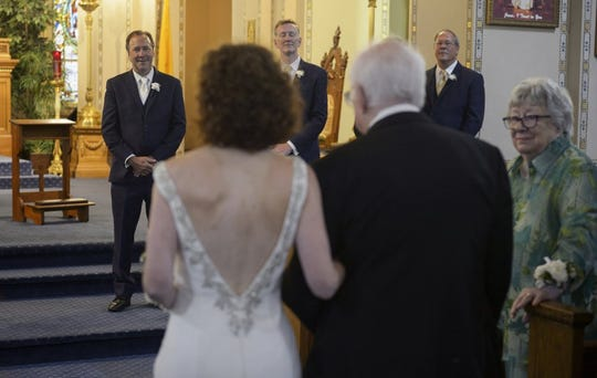 Before Tropical Storm Barry makes landfall, Associated Press staff photographer Gerald Herbert, background left, watches his bride, Lucy Sikes, walk down the aisle at Mater Dolorosa Catholic Church in New Orleans, Friday, July 12, 2019. (Max Becherer/The Advocate via AP)