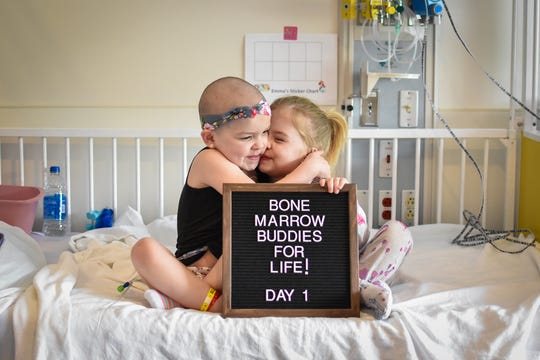 Emma (left) and Paisley Baxter are sisters bound not just by family but also by a life-threatening illness. Emma was born with a disease that can make her very sick and has put her life in danger several times. It's hoped that her younger sister's bone marrow donation will change all that. They're holding a sign on the first day of marrow transfer.