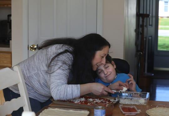 Giana Bisnett, 11, makes homemade pizza with her mother Dana Bisnett in their Greece home. Giana has spina bifida.