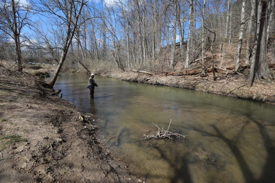 Peter Paulsen of Victor wades into Irondequoit Creek to fish during the first day of trout season at Powder Mills Park in Perinton on Wednesday, April 1, 2020. Most fisherman gave more than the six feet requirement for social distancing.