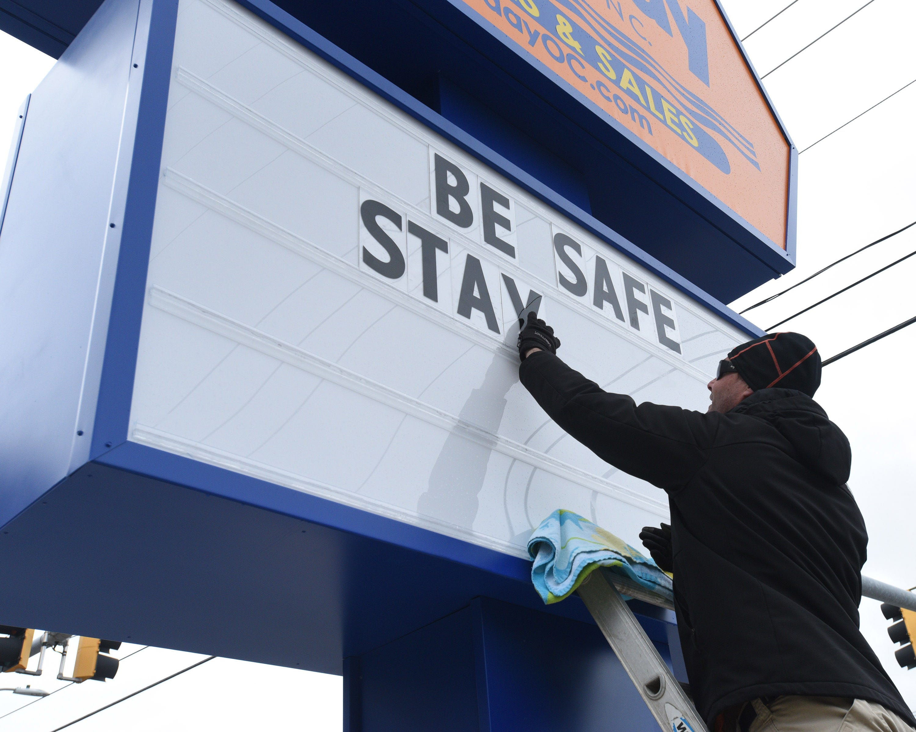 Todd Chandler of Ocean City places BE SAFE, STAY HOME letters on the sign at Holiday Real Estate Inc. at 77 Street in Ocean City on Wednesday, April 1, 2020.