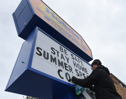 Todd Chandler of Ocean City places BE SAFE, STAY HOME letters on the sign at Holiday Real Estate Inc. at 77 Street in Ocean City on Wednesday, April 1, 2020 .