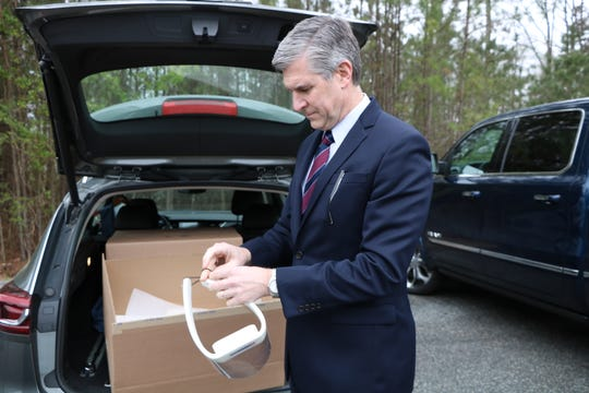 Michael Franklin, president and CEO of Atlantic General Hospital demonstrates how a doctor or nurse might use Hardwire's face shield on March 31, 2020 in Pocomoke City, Maryland. Franklin has dozens of face shields in his trunk that are still being distributed to healthcare workers at AGH.