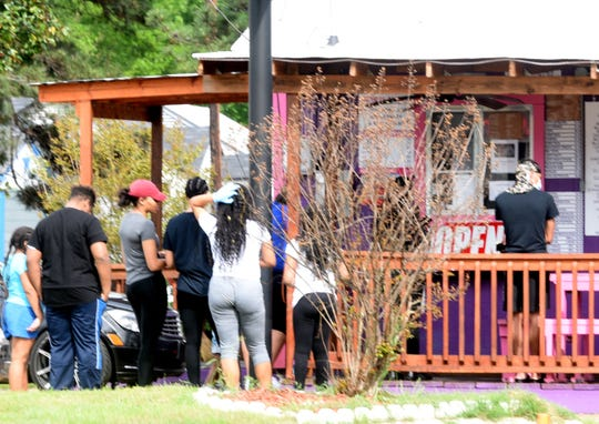 People clustered together at a store on Jewella Ave. Wednesday afternoon, April 1, 2020 in Shreveport.
