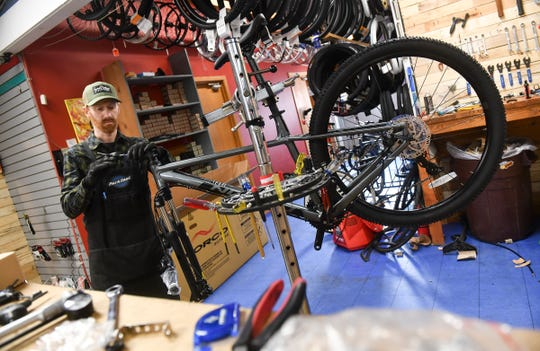 Mike Rathlisberger repairs a bicycle Wednesday, April 1, 2020, at Fitzharris Ski, Bike and Outdoor in St. Cloud.