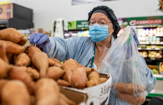 Patricia Williams, 83, wears gloves and a mask as she picks out some sweet potatoes at Ramsey's Cash Saver, Tuesday, March 31, 2020.