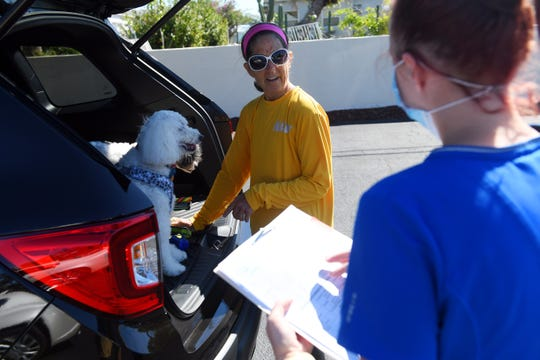 Deb Guy (right), of Vero Beach, discusses her dog's medication with veterinary technician Alexis Jackson on Wednesday, April 1, 2020, during a curbside visit to Dr. Dan's Animal Hospital in Vero Beach. Because of the continued spread of COVID-19, the animal hospital decided to go to a curbside format to limit the exposure time between staff and pet owners.