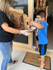 Jennifer Harris, a kindergarten teacher at West Gate K-8, delivered a pizza kit to student, Robert Kiernan, 8, Friday before virtual learning began Monday.