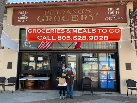 Employee Cameron Lum, left, and co-owner Jim Rice wear masks as they make curbside deliveries of food and groceries at Peirano's Market & Delicatessen in downtown Ventura. The combination restaurant and Italian market opened last fall in the historic Peirano's Grocery building.