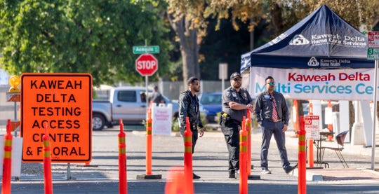 Security guards direct traffic as Kaweah Delta nurses collect nasal swabs for COVID-19 testing on Wednesday, April 1, 2020 at outdoor drive-up collection stations on Floral Street in Visalia, Calif. Appointments are required.
