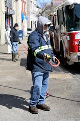 Joe Desiena with the City of Yonkers Department of Public Works uses a hose to disinfect a bus stop on South Broadway in Yonkers, April 1, 2020.