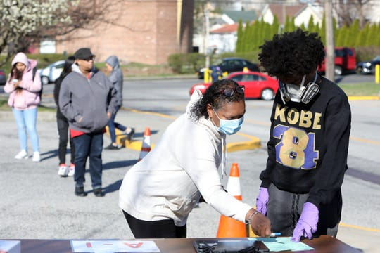 Odette Addison and her son David, 16, a junior at Thornton High School check out a laptop April 1, 2020 at Holmes Elementary School in Mount Vernon. Mount Vernon City School District faculty members distributed laptops to students in need for electronic learning during the coronavirus pandemic.