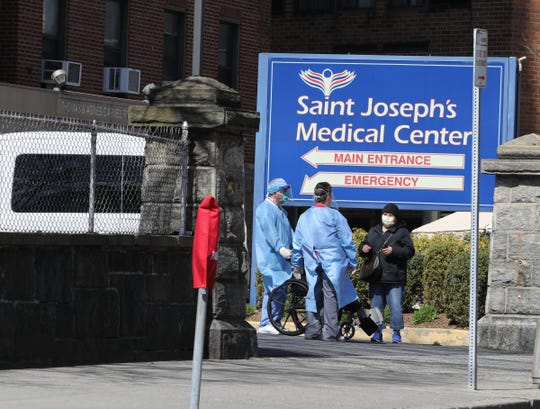 Hospital staff in protective gear at Saint Joseph's Medical Center in Yonkers, chat with a pedestrian along South Broadway, April 1, 2020.