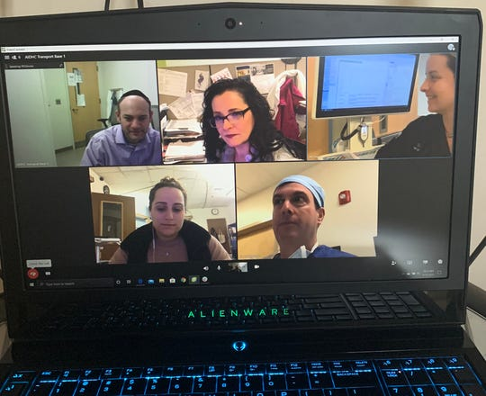 "A team of doctors and nurses at Nemours/Alfred I. duPont Hospital for Children conduct ""virtual rounds"" due to the social distancing restrictions that the coronavirus has imposed. While some like Dr. Patrick Barth (bottom right) may still be walking around the intensive care unit, other specialists can hear the latest on their patients remotely and advise the best care."
