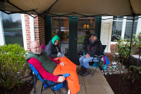 John Dean, left, his sister Elizabeth Thompson, center, and her husband Michael Thompson sit outside the room of Dean's father, Rev. John W. Dean, at Delaware Hospice in Milford. Due to the spread of the coronavirus, family members are forced to visit from outside patients' rooms. John Dean sits outside his father's room two to four hours a day.