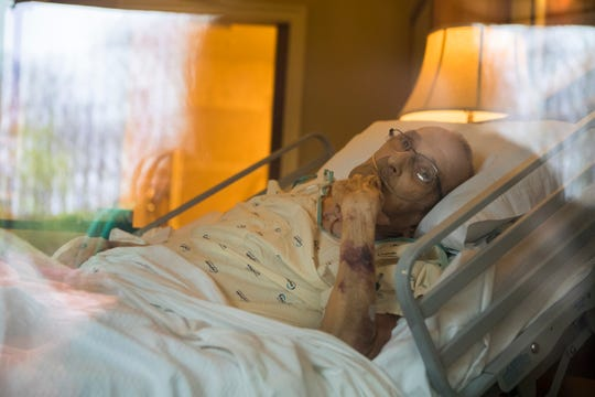 Rev. John W. Dean lies in his bed at Delaware Hospice in Milford. Unable to have his family in the room because of the threat of COVID-19, he watches and waves from his bed.