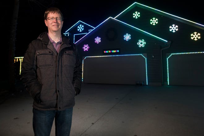 Andrew Konkol stands in front of his musical light display on Tuesday at his home in Grand Rapids. Konkol is running a special light show as a way to boost community morale during the COVID-19 pandemic.