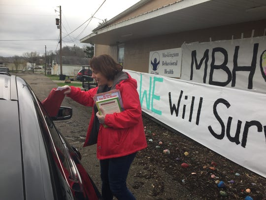 Kris Headley, chief prevention officer at Muskingum Behavioral Health, hands out books and care packages to help residents cope with the stress of the COVID-19 pandemic.