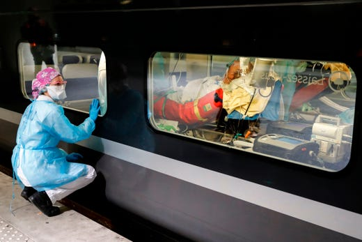 A medical staff watches from a platform of the Gare d'Austerlitz train station on April 1, 2020 in Paris through the window of a medicalized TGV high speed train before its departure to evacuate patients infected with the COVID-19 from Paris' region hospitals to other hospitals in the western France Brittany region where the outbreak has been limited so far.  France has been on lockdown since March 17 in a bid to limit the contagion caused by the novel coronavirus, a situation it has extended until at least April 15.