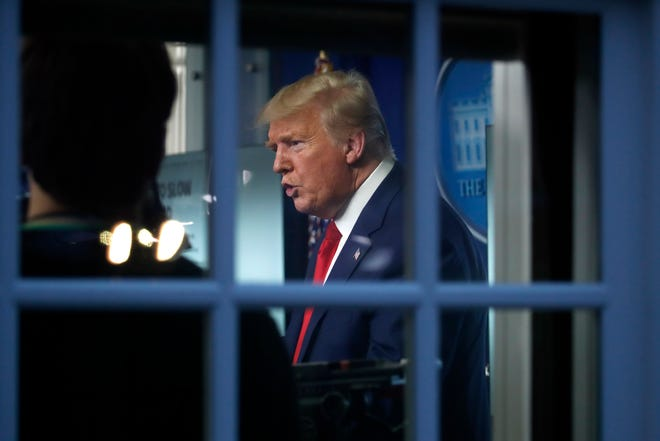 As seen through a window, President Donald Trump speaks about the coronavirus in the James Brady Press Briefing Room of the White House, Tuesday, March 31,