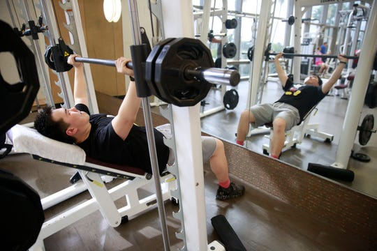 In this March 10, 2020, file photo, Darren Chen lifts weights at Life Time Athletic gym in Boca Raton, Fla.