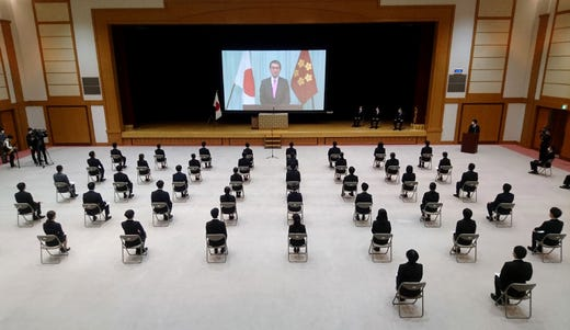 New employees of Japan's defense ministry sit on chairs spaced apart for social distancing due to concerns over the spread of COVID-19 coronavirus, as they watch a video message of Defense Minister Taro Kono during a ceremony in Tokyo on April 1, 2020.