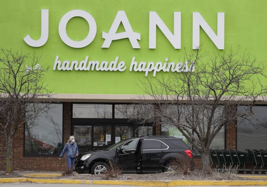 A woman walks back to her vehicle after reading a sign stating Joann Fabrics and Crafts was on Wednesday in Grand Chute.