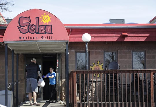 A customer picks up a lunch order at Solea Mexican Grill in Neenah. It remains open for carry-out.