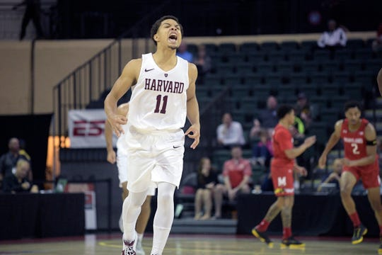 Harvard guard Bryce Aiken (11) celebrates after making a three-point shot during the second half of an NCAA college basketball game against Maryland Friday, Nov. 29, 2019