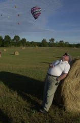Event director found a hay bale to lean against and watch balloons during the 2007 Battle Creek Field of Flight.  Trace Christenson/TheEnquirer