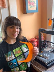 Union-Endicott High School junior Abby Winans has been making orange face shields using a 3D printer at her Endicott home. She plans to donate them to local healthcare workers.