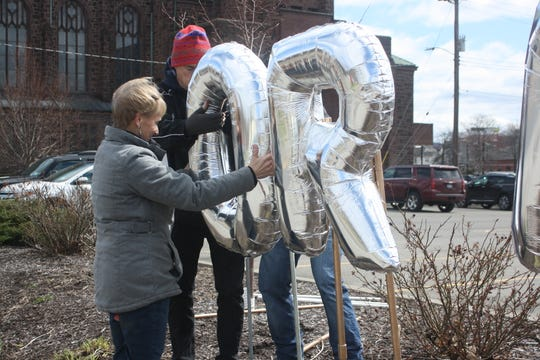 Rosemarie Kleitz and David Nealon construct a balloon sculpture outside  UHS Wilson Medical Center on Main Street in Johnson City on April 2, 2020. The balloons read HonorAndThank.com, a website where anyone around the country can post messages of appreciation, encouragement and love.
