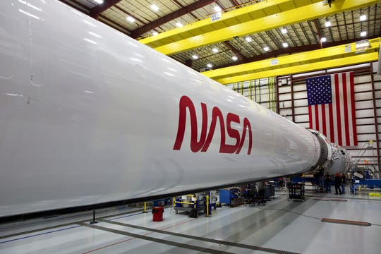 "NASA's famous ""worm"" logo is seen on a SpaceX Falcon 9 rocket at the company's Kennedy Space Center hangar. The first rocket to fly with the new logo will take astronauts to the International Space Station."