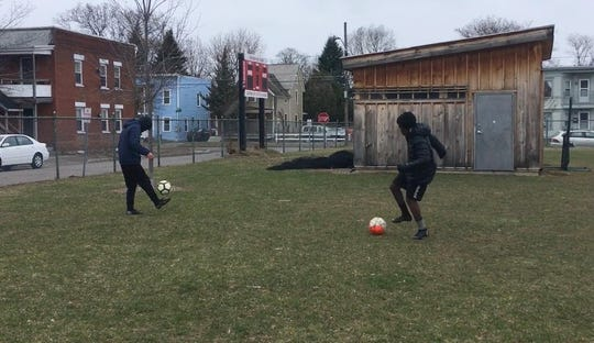 Oliver Alimasi, 15, right, and Kong Say, 15, both of Burlington, play with individual soccer balls they brought to Roosevelt Park in Burlington on Thursday, April 2, 2020.