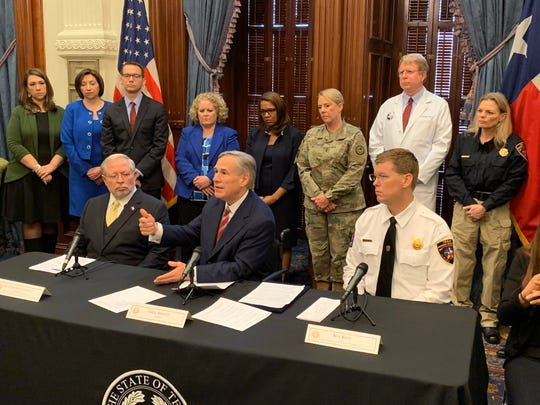 Gov. Greg Abbott, flanked by state health services commissioner John Hellerstedt, lefand Nim Kidd, Texas Emergency Management Division chief.
