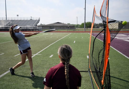 """Kiersten Lopez, left, hits softballs into the net, Thursday, March 26, 2020, at Sinton High School. """"We were all so excited about the season,"""" Lopez says, """"I feel like the virus got in the way of that."""""""
