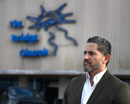 "Pastor Joel Garza stands in front of his church, Wednesday, April 1, 2020, at The Bridge Church in Robstown. ""These are our constitutional rights,"" Garza says about continuing physically gathering for church services."