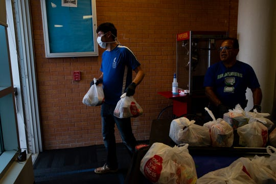 Student worker David Lopez caries bags of food out to students waiting for the Izzy's food pantry food bag giveaway behind the University Center on Thursday, April 2, 2020.