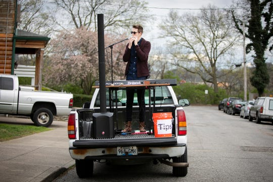 Bryan McCartney, a music teacher from Bellevue, welcomes neighbors on Clark Street to his 'Truck Bed Sing Along Tour' on Wednesday, April 1. McCartney has been singing and playing the keyboard out of the back of his truck in his Bellevue neighborhood as a way to supplement his income during the 'shelter-in-place' order.